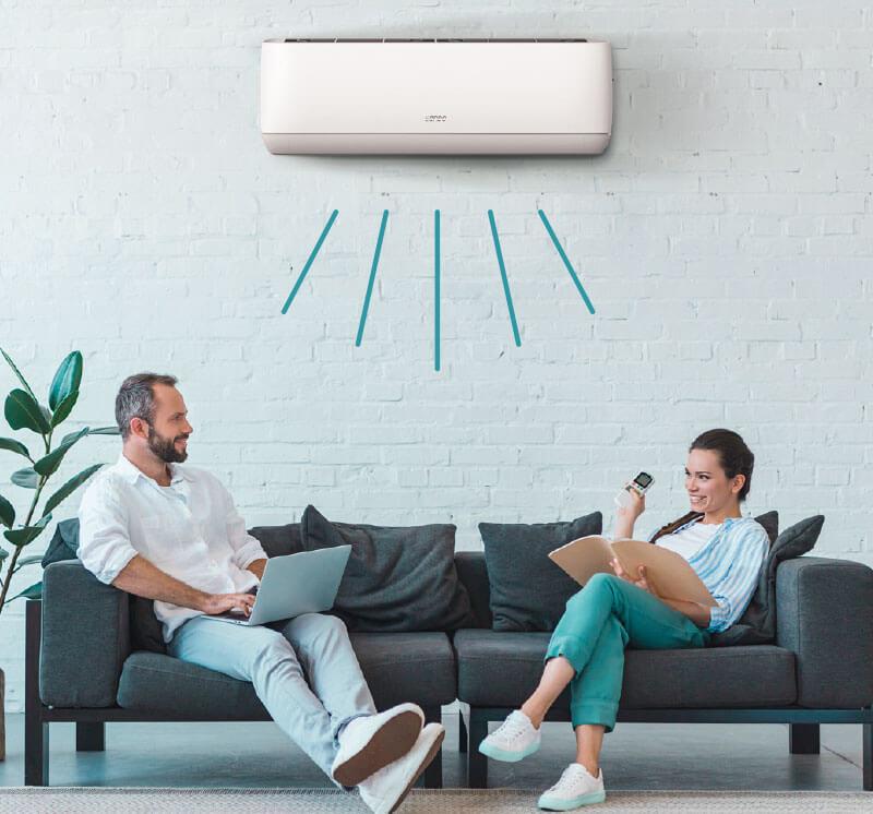 2 menschen sitzen auf einem Sofa in einem Raum mit Sendo AEOLOS Klimaanlage